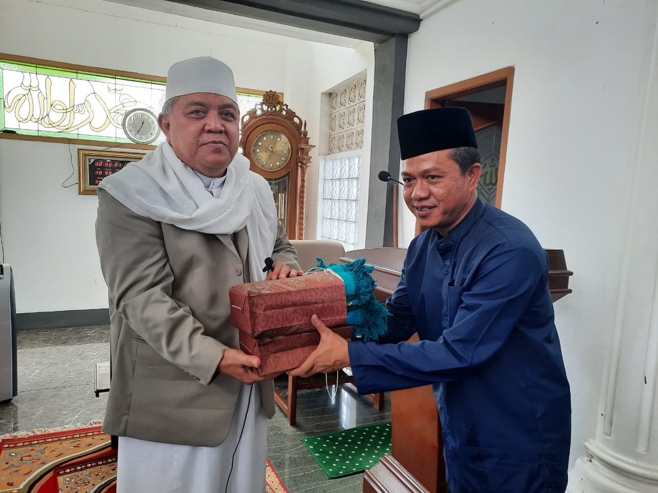 Bupati Bandung terpilih HM Dadang Supriatna menyerahkan cindera mata kepada Pimpinan Ponpes Darul Ma'arif KH Sofyan Yahya, di Desa Rahayu, Kec Margaasih, Kab Bandung, Jumat (12/2/2021).
