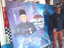 """R Cahyadi dengan lukisannya """"Wirjaatmadja Perintis Bank Pribumi"""" tahun 2021'di.Galeri Salaras. (Foto : Sopandi/dejurnal.com)"""
