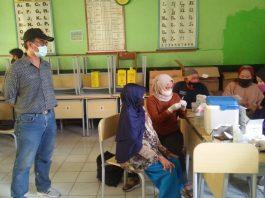 Plt Kades Sukamukti Kecamatan Katapang Yadhi Kowara sedang meninjau vaksinasi di SDN Sekepeuris 1. (Sopandi/dejurnal.com)